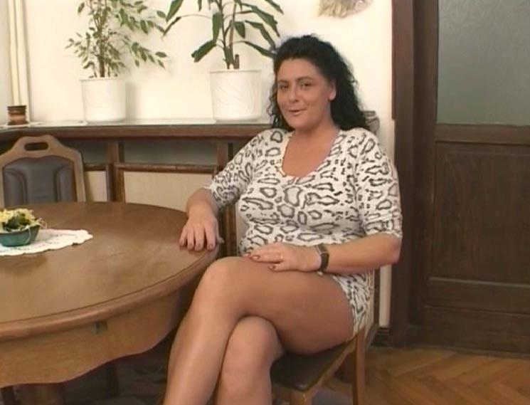 reife dicke Brünette sitzt auf Stuhl